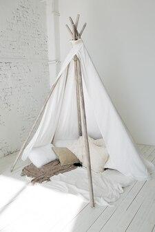 Parede de tijolo moderna e moderna e casa para crianças em forma de tenda.
