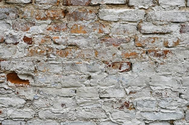 Parede de tijolo rachado velho branco