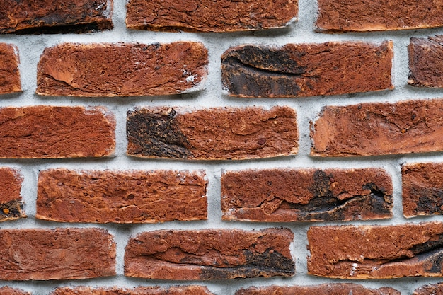 Parede de tijolo vermelho. a fachada do edifício com gesso novo. textura de alvenaria.