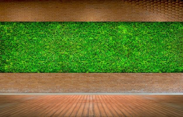 Parede de tijolo vermelho com fundo verde fresco da grama