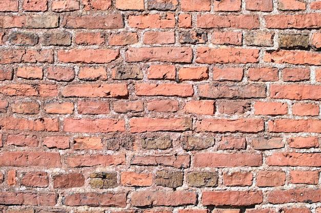 Parede de tijolo vermelho, incluindo caiação e descoloração de alguns tijolos, em construção para plano de fundo.