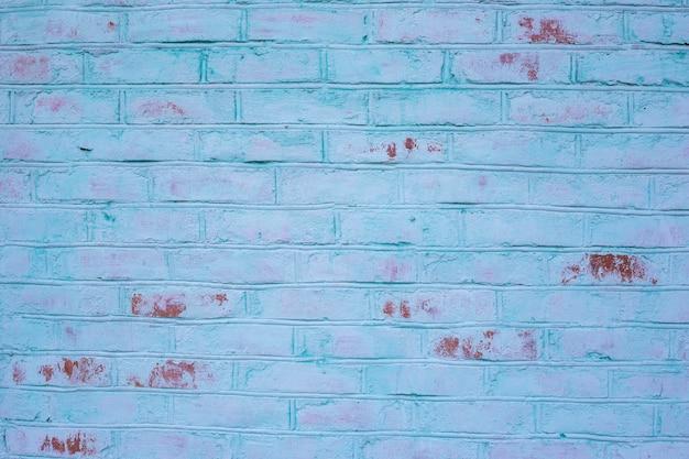 Parede de tijolo vermelho pintado de turquesa, close-up. parede de tijolo vermelho com pintura azul-petróleo, fundo