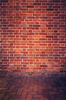 Parede de tijolo vermelho retrô e piso de tijolo.