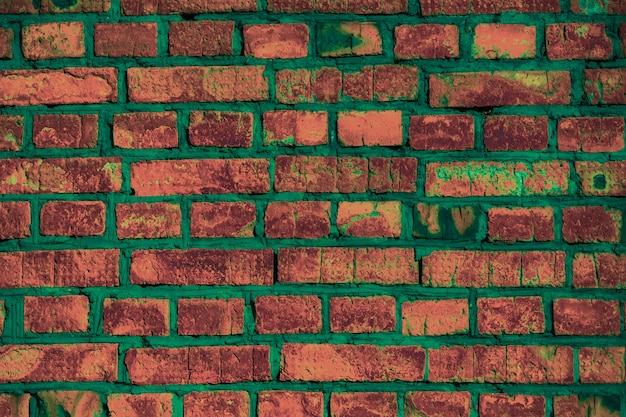 Parede de tijolos antigos. fileiras ásperas de borgonha e laranja manchado tijolo. concreto verde.
