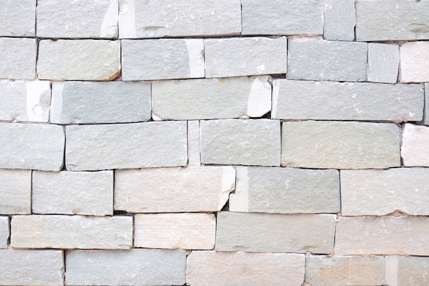 Parede de tijolos cinza e fundo da parede de pedra areia áspera