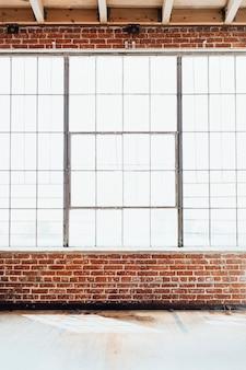 Parede de tijolos com grande janela de vidro, fundo interior