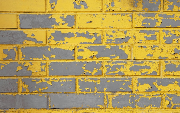 Parede de tijolos de concreto cinza desgastada por grunge antigo com escamas, manchas e defeitos de tinta amarela