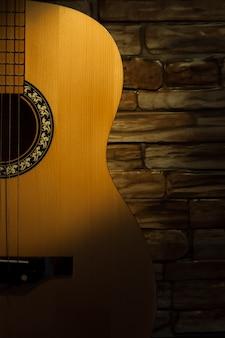 Parede de tijolos de guitarra acústica no escuro, um feixe de luz ilumina.