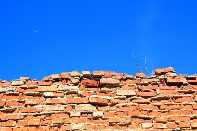 Parede de tijolos destruídos entre ervas