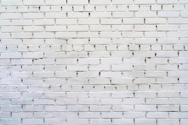 Parede de tijolos é pintada de branco