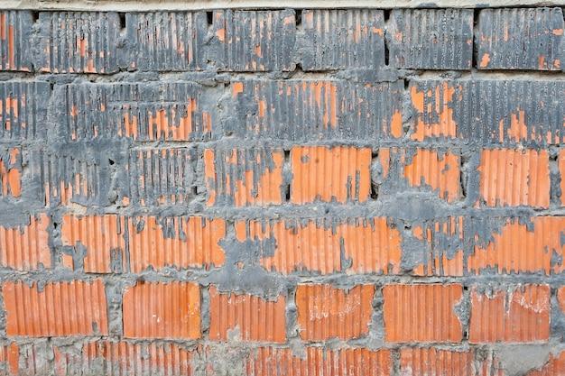 Parede de tijolos listrados de laranja com uma espessa camada de cimento entre e sobre eles