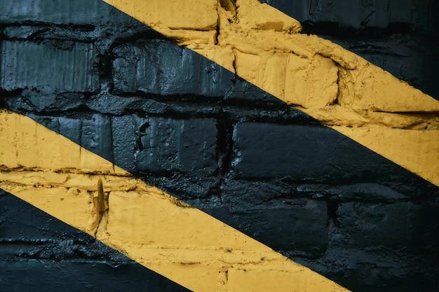 Parede de tijolos pretos com listras amarelas na academia