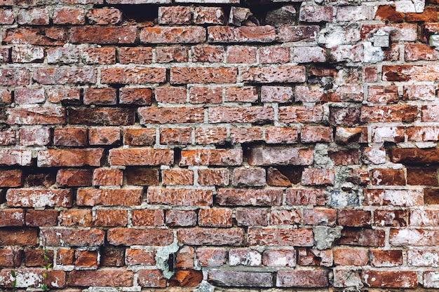 Parede de tijolos vermelhos do vintage sujo em um close-up.
