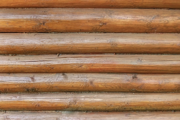 Parede de uma casa feita de toras horizontais de madeira natural