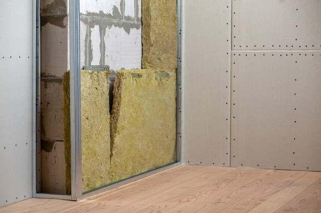 Parede de uma sala em reforma com isolamento de lã de rocha mineral e armação de metal preparada para placas de drywall.