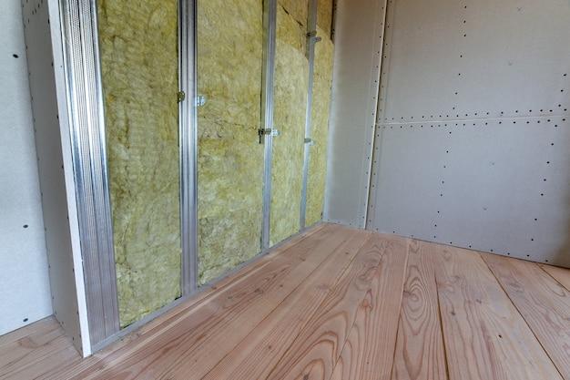 Parede de uma sala em reforma com isolamento de lã de rocha mineral e estrutura metálica preparada para placas de drywall.