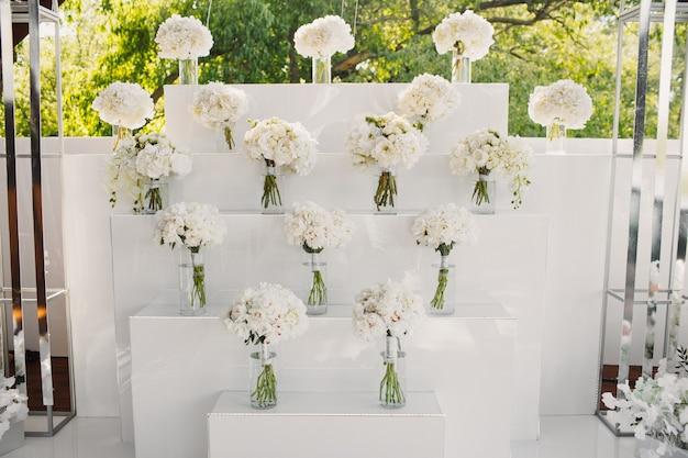 Parede decorada por buquês de flores brancas