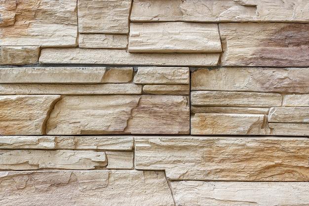 Parede decorativa de uma pedra rasgada envernizada (tijolo) como um fundo ou uma textura.
