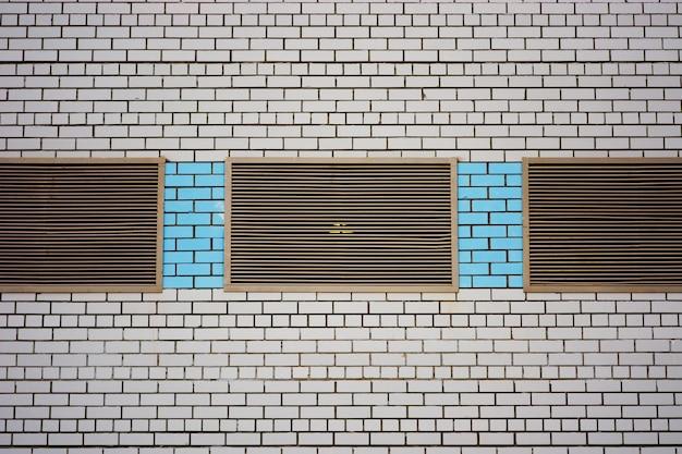 Parede do edifício cooperativo para loja, oficina, garagem e outras necessidades industriais. fundo da parede de tijolo branca com janelas fechadas metálicas e inserções de close-up de tijolo azul.