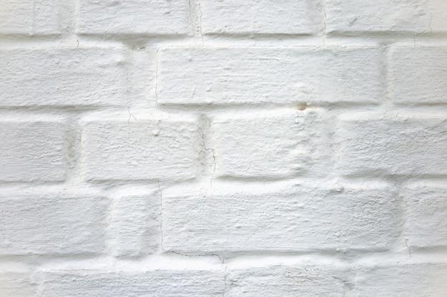 Parede do edifício de tijolos pintados em solução de limão branco
