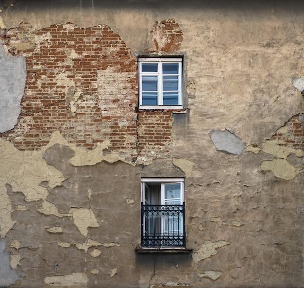 Parede do edifício sujo velho com duas janelas