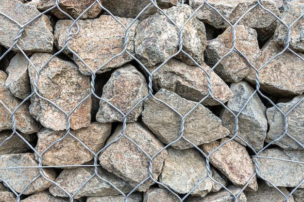 Parede estrutural - pedra de granito atrás de uma rede de malha, parede