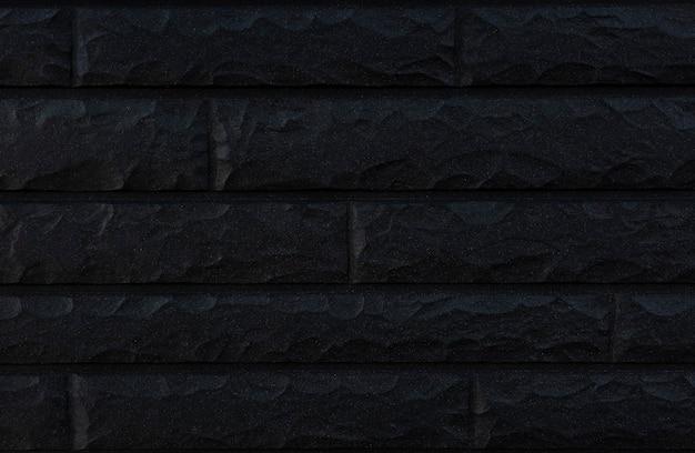 Parede exterior de alvenaria preta em estilo moderno iluminada com luz suave e sua superfície em alto relevo alternada.