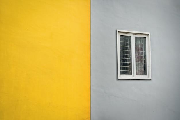 Parede externa amarela e cinza com janela. parede externa em cor duotônica.