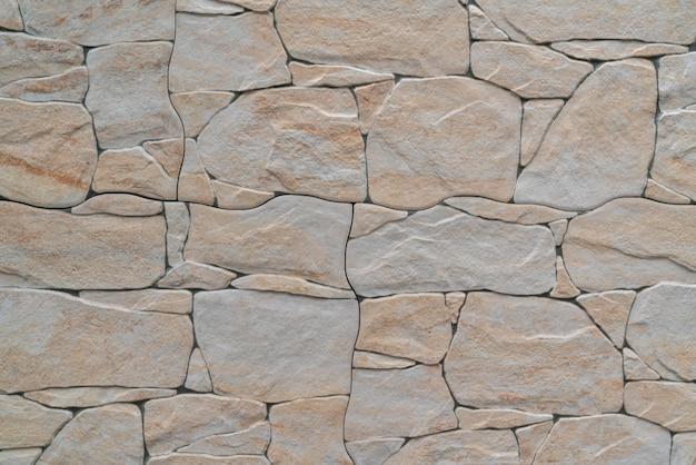Parede feita com pedras cinza e laranja de tamanhos diferentes