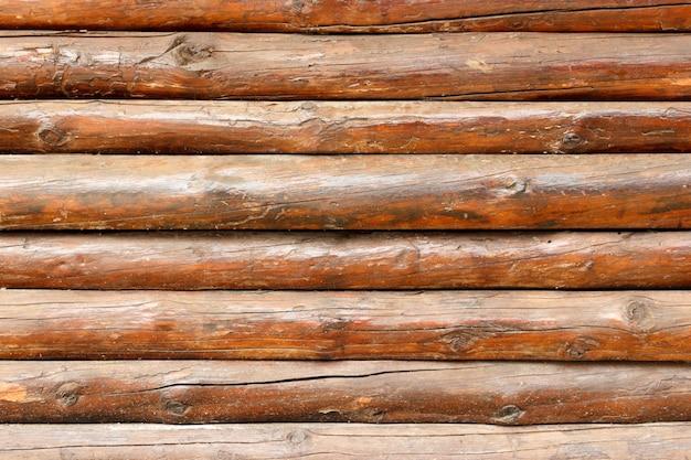 Parede feita de toras de madeira. textura de cerca de vigas de madeira