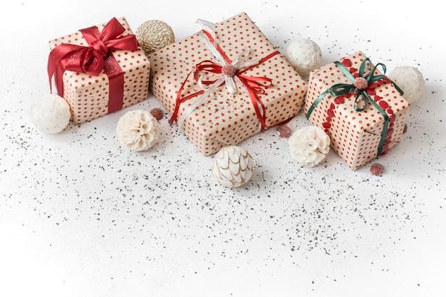Parede festiva de ano novo branco com presente amarrado com fita vermelha.