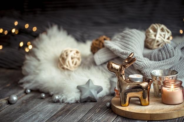 Parede festiva de natal com cervo de brinquedo, parede desfocada com luzes douradas e velas, parede festiva na mesa de deck de madeira