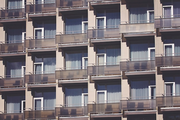Parede frontal de edifício moderno com padrão repetido de janelas e varanda
