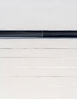 Parede interna branca minimalista com espaço de ventilação