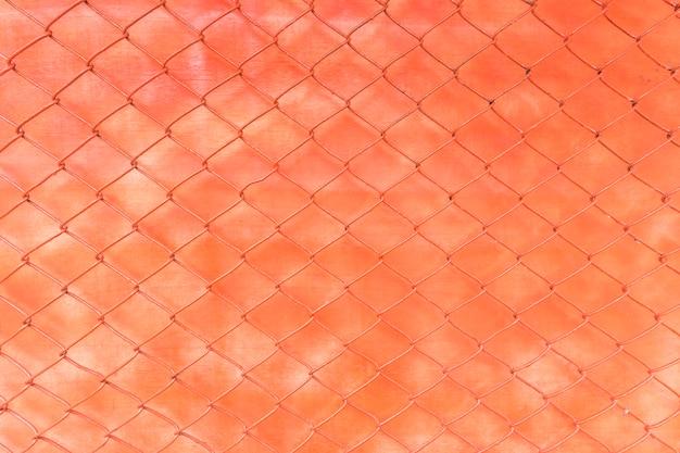 Parede laranja brilhante debaixo de uma cerca de malha de arame como pano de fundo