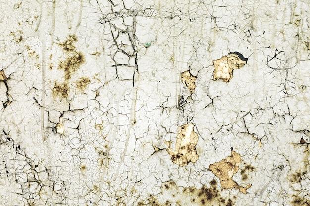 Parede pintada com tinta danificada e rachaduras