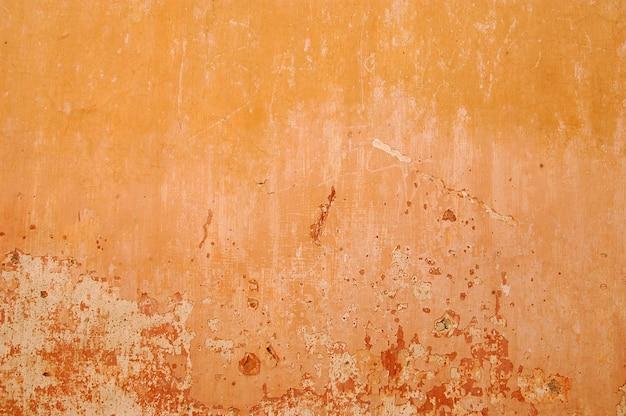 Parede pintada com tons de laranja, textura de fundo rachado, parede velha