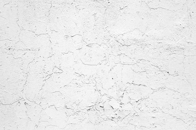 Parede pintada de branco com tinta danificada.