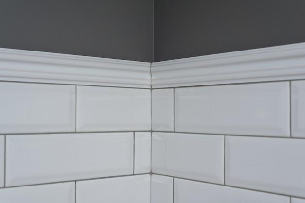 Parede pintada de cinza, parte da parede é revestida de azulejos