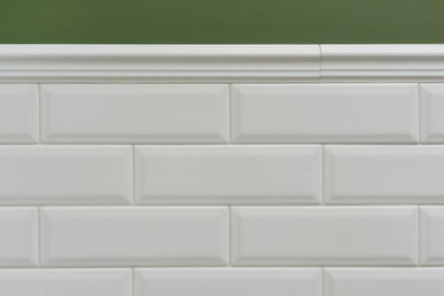 Parede pintada de verde, parte da parede é coberta de azulejos pequenos tijolos brilhantes brancos