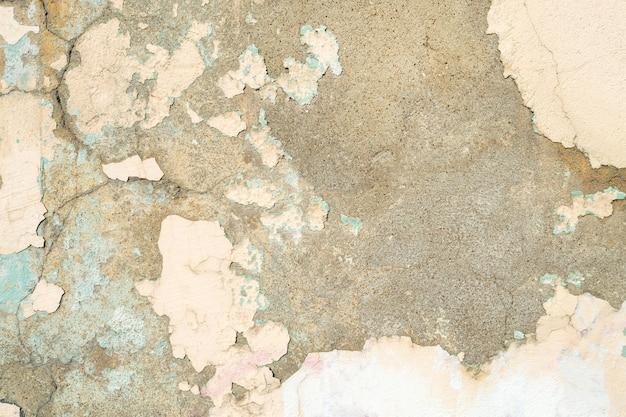 Parede pintada em bege. cor envelhecida com tinta lascada. textura rachada, fundo abstrato.