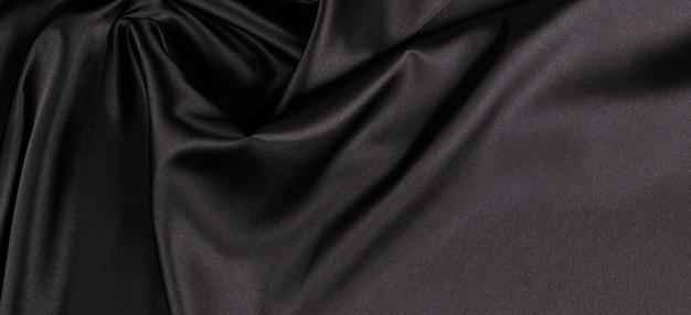 Parede preta elegante bonita com cortinas e dobras onduladas de textura de material de cetim de seda. vista do topo