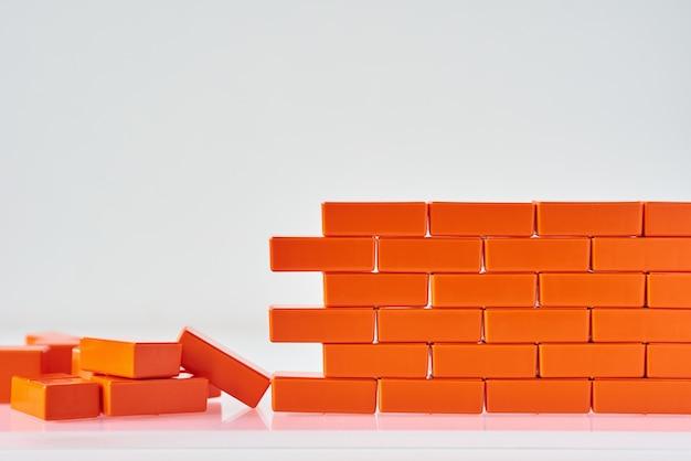 Parede quebrada feita de blocos de brinquedo em um fundo branco