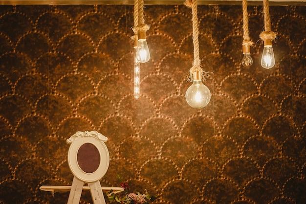 Parede quente decorado com lâmpadas e cordas e espaço livre para colocar o texto em um quadro vazio