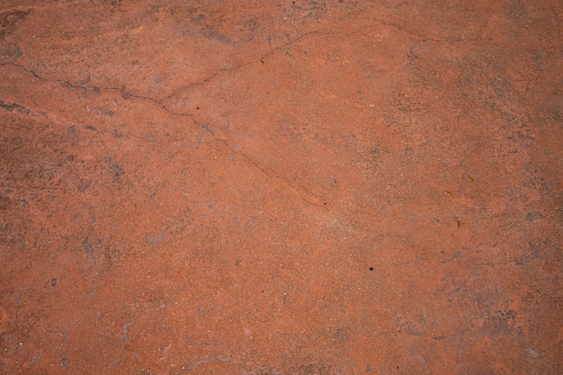 Parede rachada velha ou textura e fundo alaranjados do assoalho do cimento