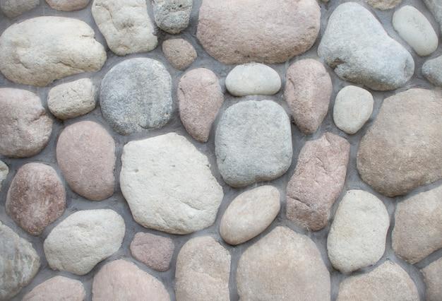 Parede redonda textura de pedra de pedra. grandes pedras na estrada.