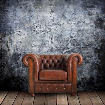 Parede suja com poltrona clássica de couro marrom e madeira velha