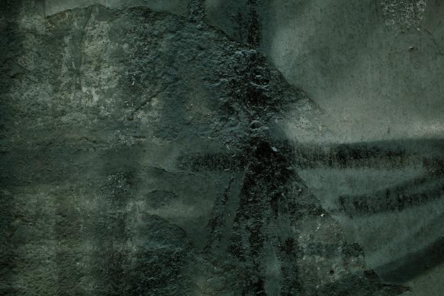 Parede velha escura e suja com pinceladas confusas na tinta verde em uma superfície de concreto