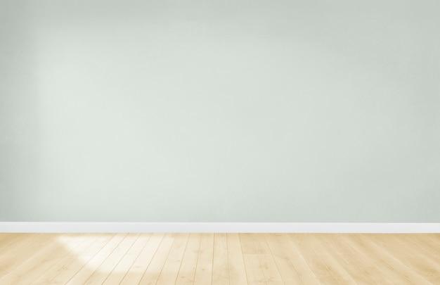 Parede verde clara em uma sala vazia com piso de madeira