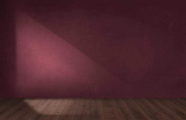 Parede vermelha da borgonha em uma sala vazia com piso de madeira